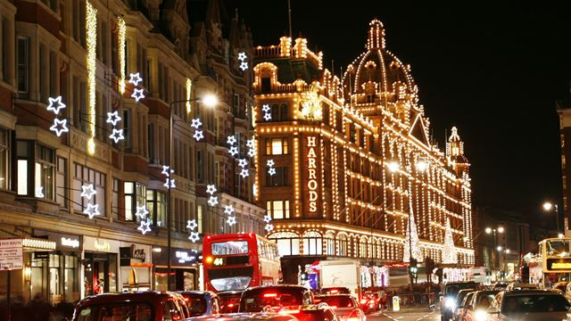 Photo of a road with Harrods store decorated in Christmas lights.