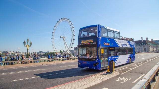 Blue double-decker bus driving past South Bank and the London Eye.