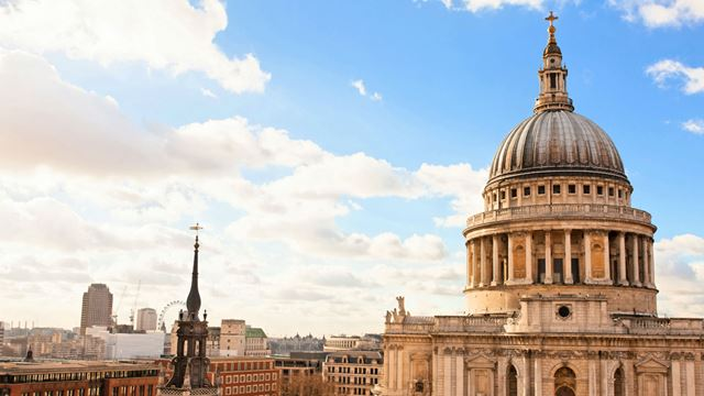 A photo of St Paul Cathedral's dome with panoramic view of London and blue skies.