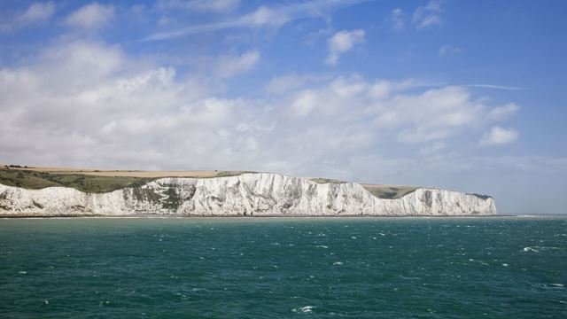 A photo of the White Cliffs of Dover, with blue skies and water surrounding it.