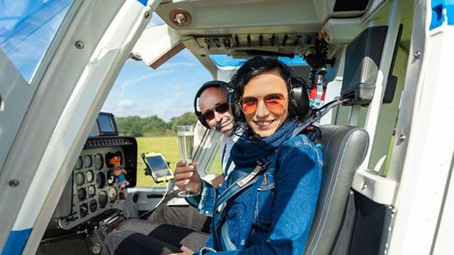 Женщина сидит в кресле второго пилота рядом с пилотом с бокалом шампанского.