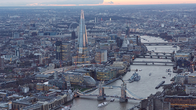 An aerial view of central London at sunset, taken from the helicopter, showing the Thames, Tower Bridge and The Shard.