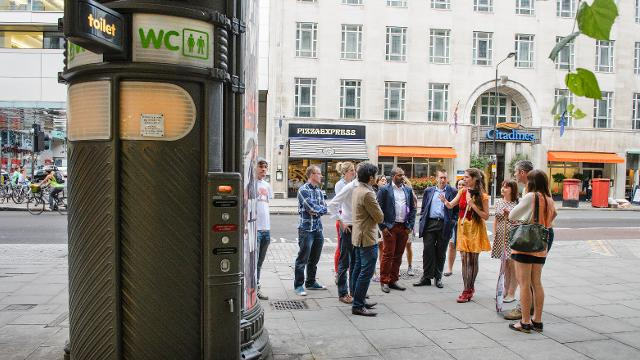 Tour group stand outside a public toilet in London