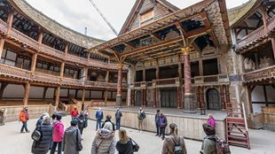 A small group of people, wearing face coverings, gather in front of the stage at Shakespeare's Globe Theatre.