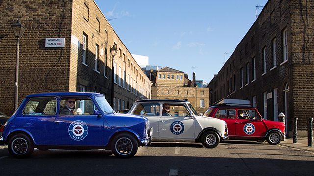 Three minis, branded with Small Car Big City logos – one blue, one white and one red – line up on a London street.
