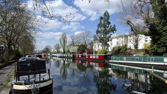 Looking along a canal, with canal boats on both sides of the canal, on a bright day.