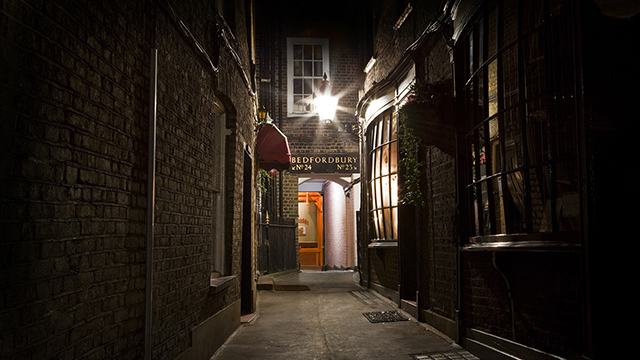 A narrow, darkened alley leads to a dimly lit pub at night, which is part of the London Grim Reaper Tour.