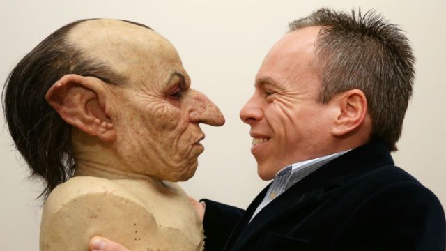 Actor Warwick Davis viewing prosthetic mask used in Harry Potter films