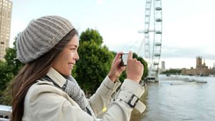Woman taking a picture with the London Eye skyline.
