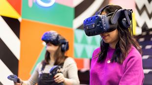 Two girls test out VR headsets in a colourfully decorated room.