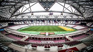 A fish-eye image of the inside of London Stadium, with West Ham United FC claret-coloured seats and a football pitch.
