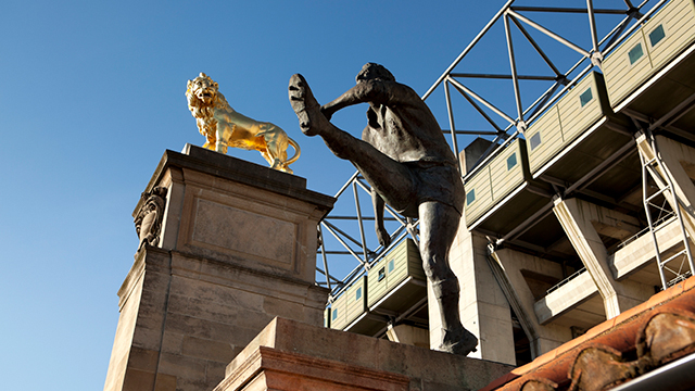 A statue of a rugby player after kicking a ball, and a gold lion statue.