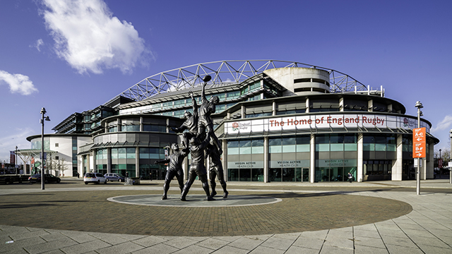 The exterior of Twickenham Stadium, with a statue of rugby players catching a ball at a lineout. Taken on a clear day.