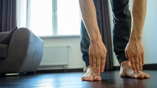 Man stretching to touch his toes in a home workout.