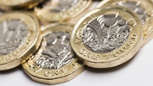 British one pound coins scattered on white surface.