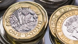 Stacks of British coins with one pound coins on top.