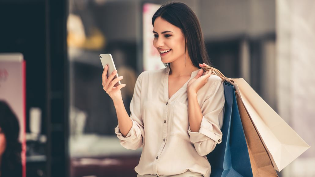 A woman looks at her phone with delight while carrying shopping bags over her shoulder.