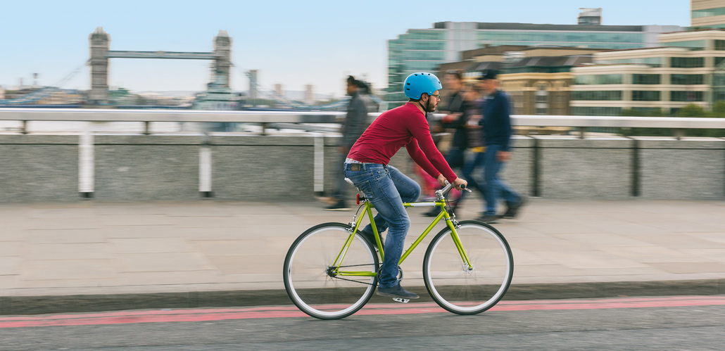 Man cycling on a green bike with Tower Bridge in background.