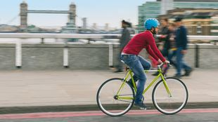 Man cycling over London Bridge with Tower Bridge in background