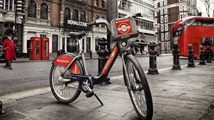 A Santander Cycle in the foreground on a pavement with a red London bus in the background