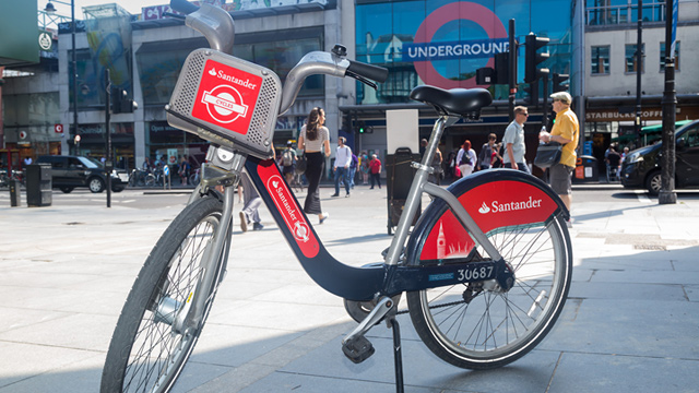 A Santander Cycle bicycle with an Underground station in the background.