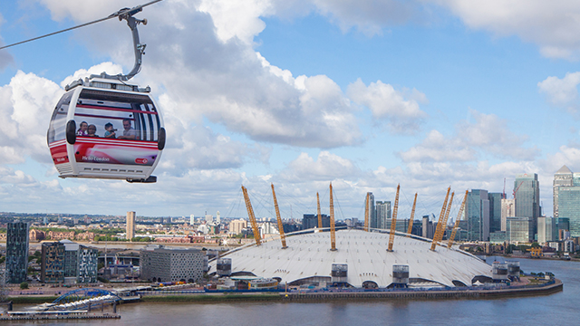 One of the cabins on the Emirates Air Line cable car moves in the air, with The O2 and river Thames in the background, on a slightly cloudy day.