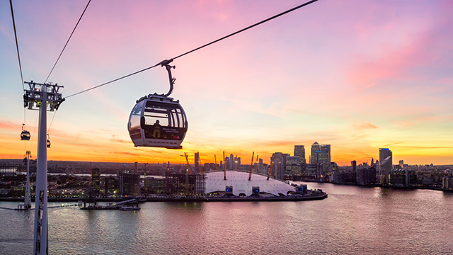 One of the Emirates Air Line cable cars rises high above the Thames at sunset, with The O2 in the background.