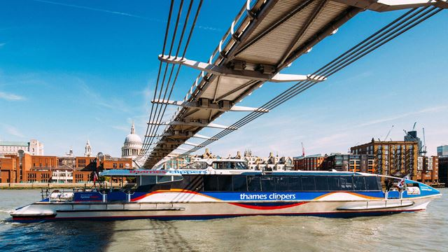 An image taken from river level as Thames Clippers' Cyclone river boat passes under the Millennium Bridge, with St Paul's Cathedral in the background.