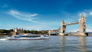 An image of Thames Clippers' Galaxy river boat approaching Tower Bridge, taken from river level.