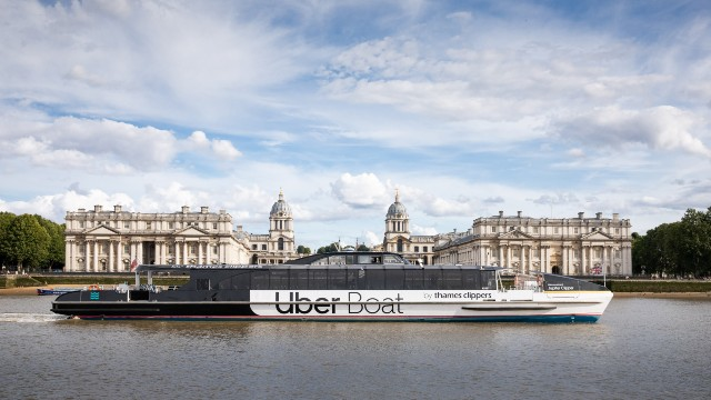 The Uber Boat by Thames Clippers river bus floats along the river Thames past the Old Royal Naval College.