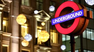 A London Underground sign lit up at night, with Christmas lights shining in the background.