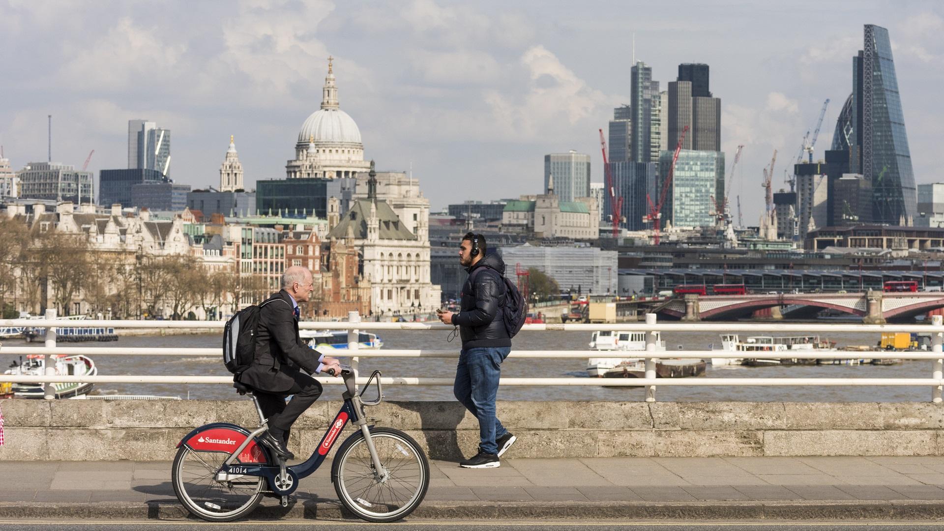 man cycling on bridge on a Santander Bike in front of London skyline