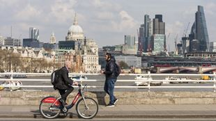 man cycling on bridge on a Santander Bike in front of London skyline