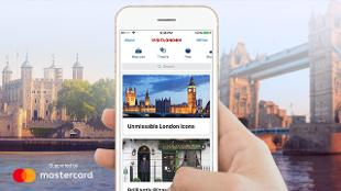 A hand holds a phone with the visit london app