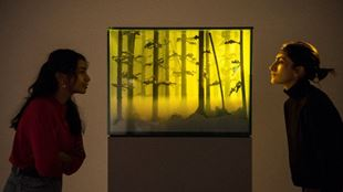 Two people standing side to side of a yellow painting of trees, looking at each other.