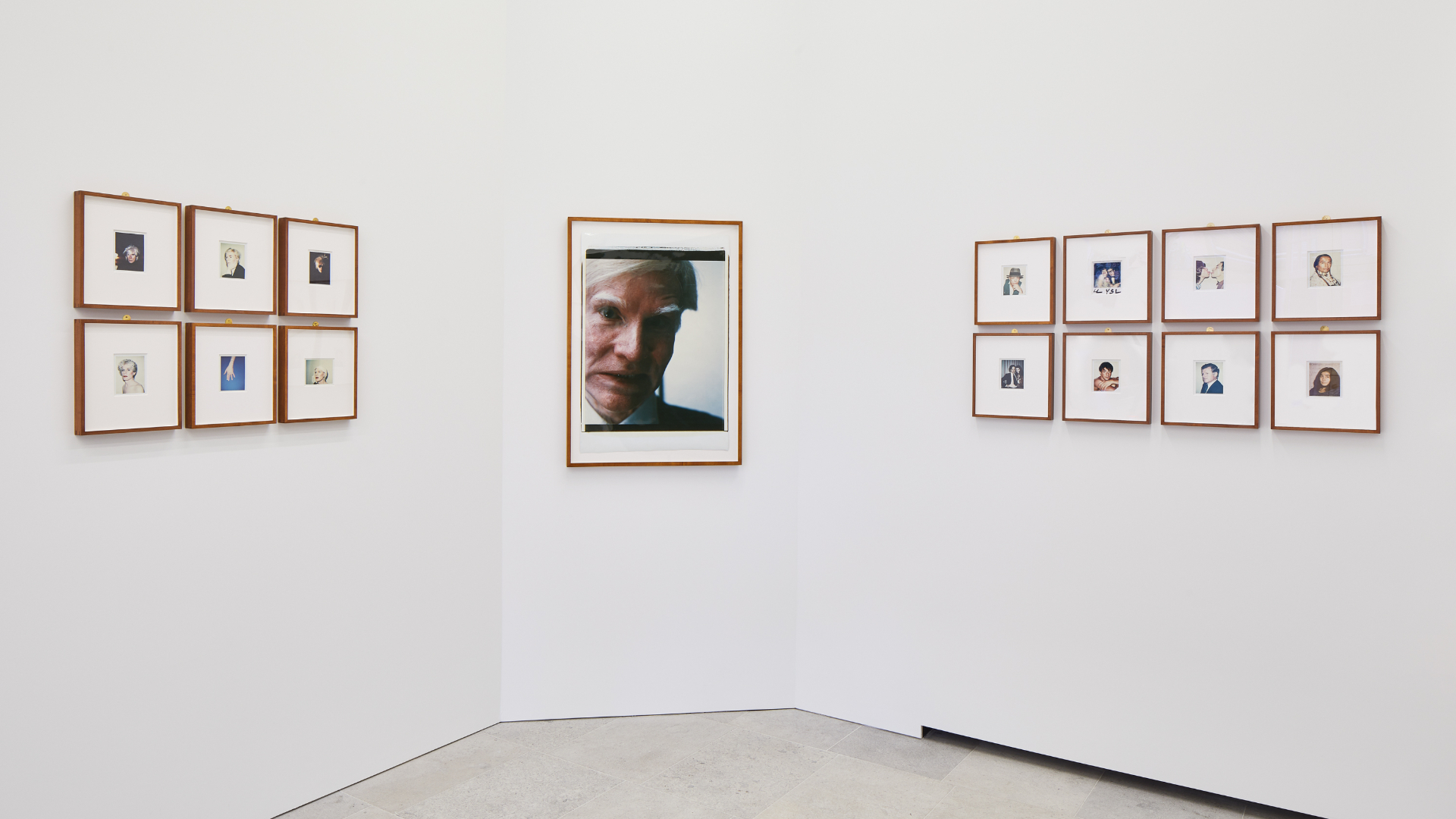 A collection of framed Polaroid photographs on a white wall, including a large self-portrait, by Andy Warhol as part of Andy Warhol Polaroid Pictures exhibition at Bastian