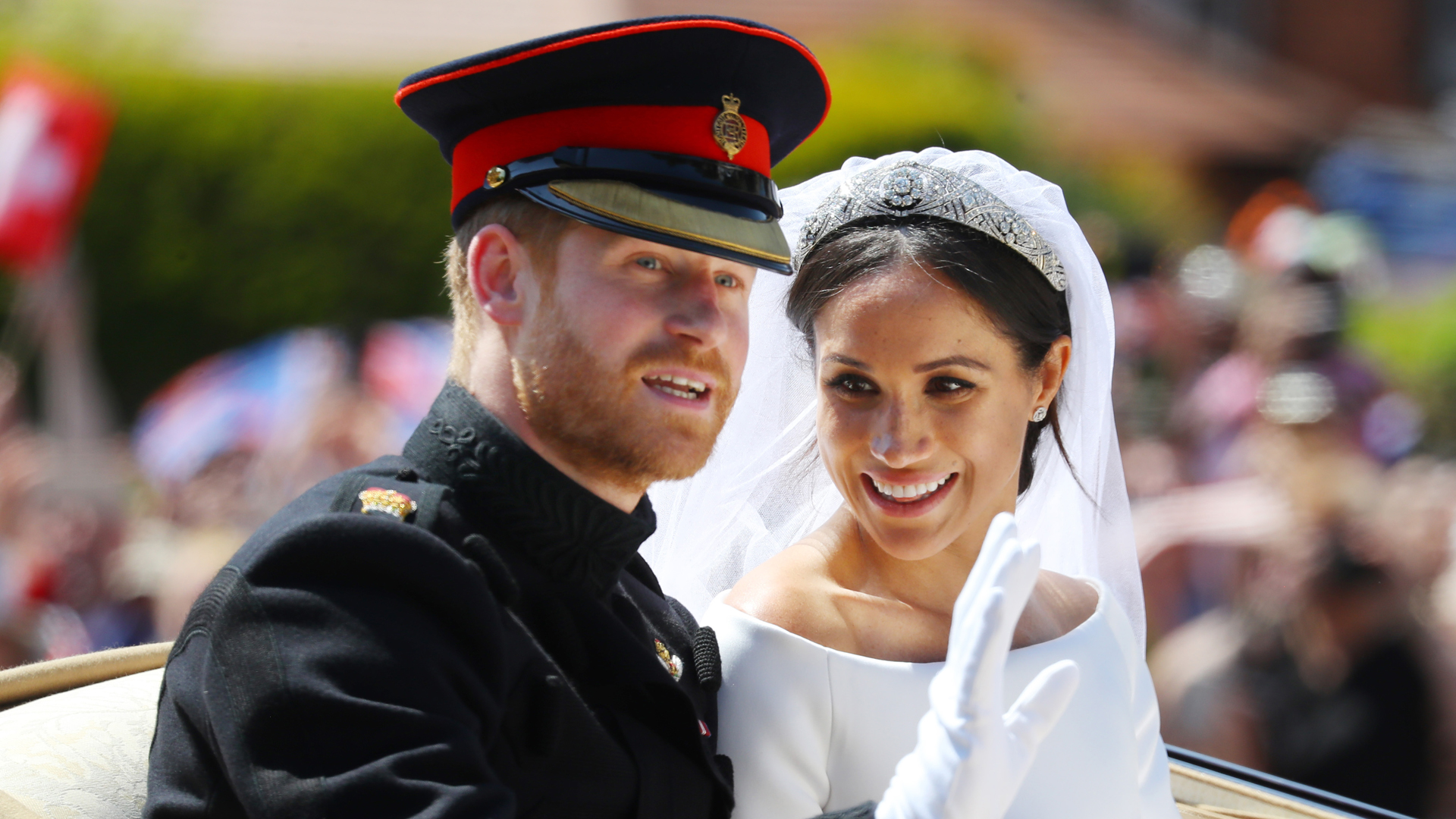 Duke and Duchess of Sussex smiling in their carriage at their royal wedding in Windsor