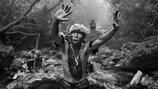 A shaman, dressed in traditional clothing, holds his hands up to the sky in a black and white photograph.