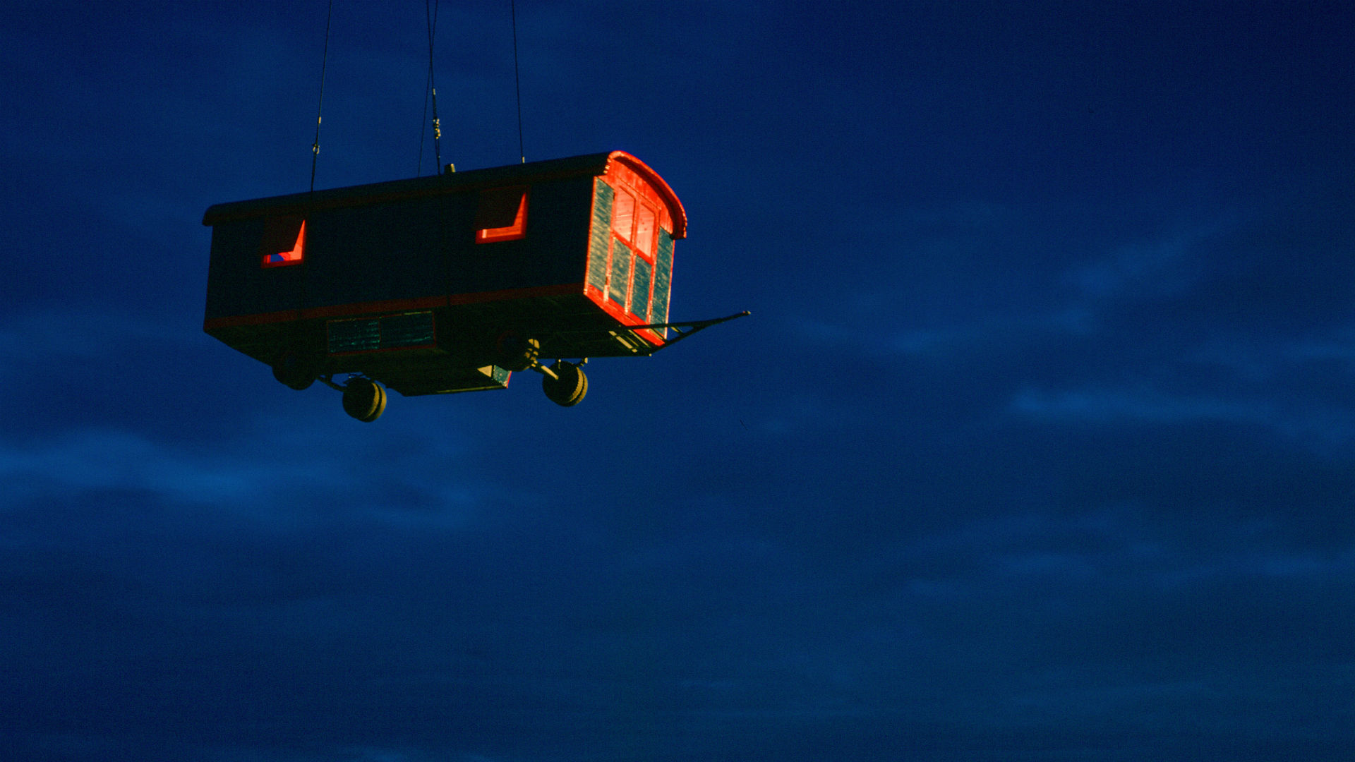 Lara Favaretto's red and blue caravan installation suspended by crane in the night sky
