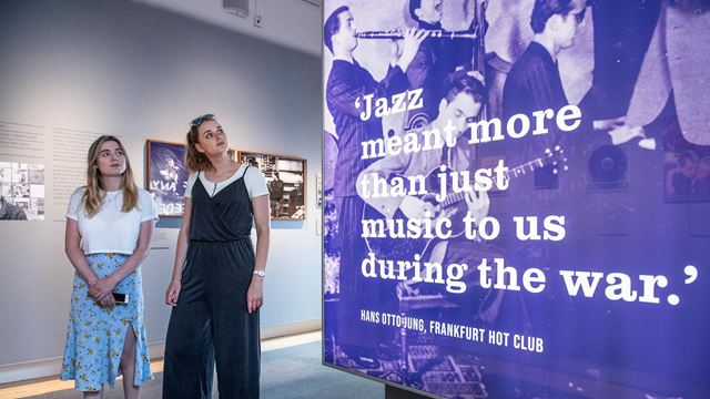 "Two women look at an image of a jazz band, with the words ""Jazz meant more than just music to us during the war."" - Hans Otto-Jung, Frankfurt Hot Club."