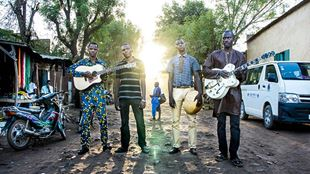 Four members of Songhoy Blues stand in a street with their instruments.