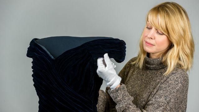 A lady wearing white gloves holds the blue velvet 'Travolta' dress.