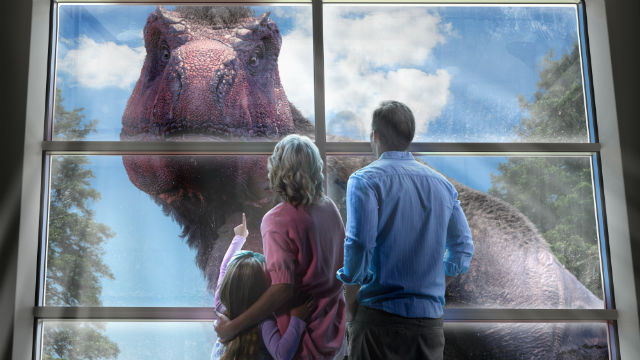 Family watch Tyrannosaurus passing in front of their window