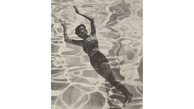 A model floats outstretched in water, which is dappled with sunlight, in a black-and-white photograph.