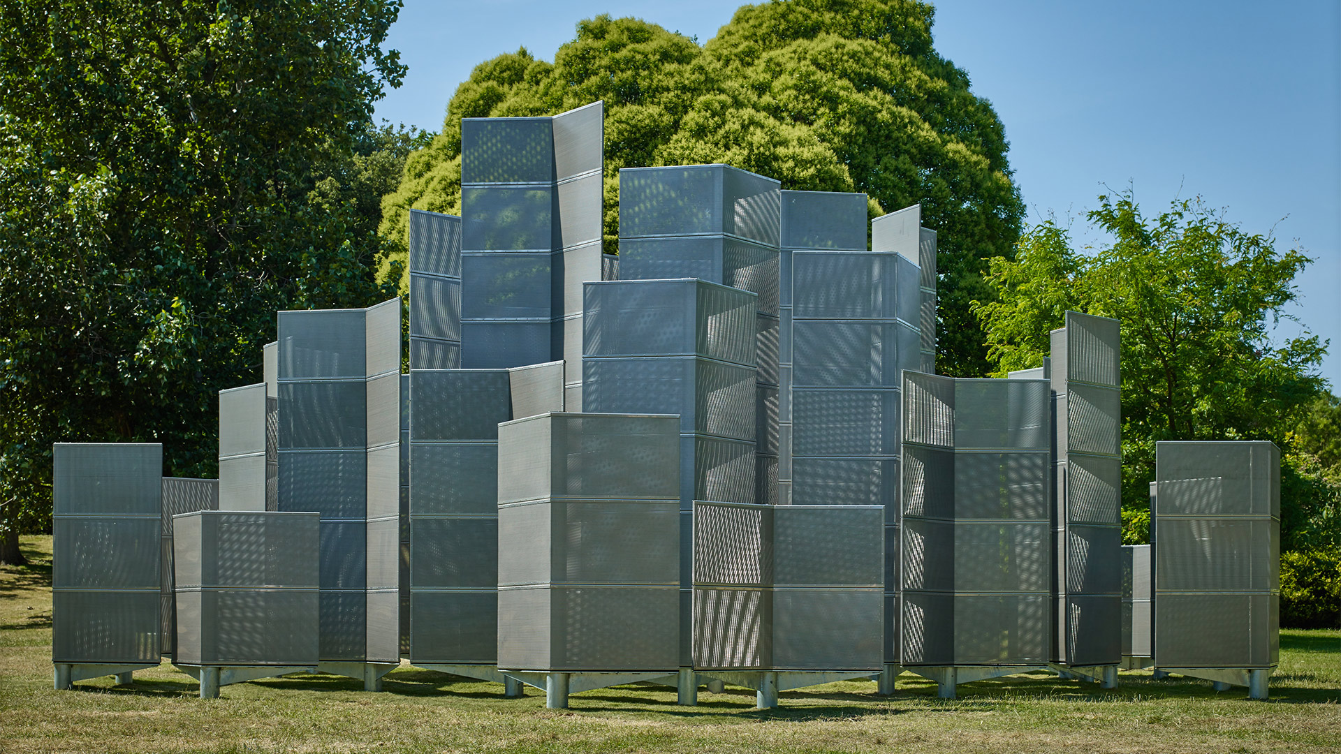 Vertical individual metallic pieces make up Optic Laybrinth, set on the grass against a backdrop of blue sky and trees.