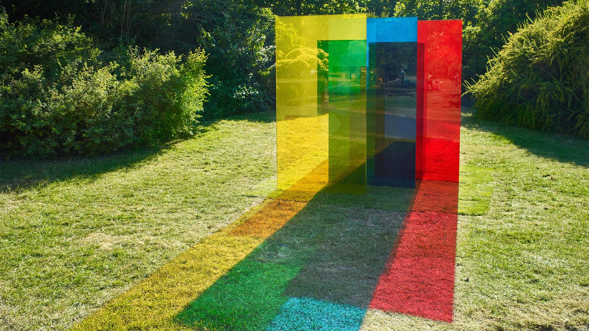 Four vertical pieces of coloured glass (yellow, green, blue and red) of varying heights, cast coloured shadows on the grass