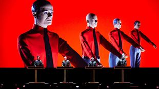Four men, dressed in black, stand at black podiums on a black stage, set against a bright red background featuring four larger figures.