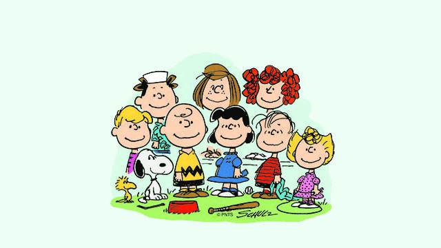 Cartoon of the characters from Peanuts comic strip standing together smiling, including Snoopy, Charlie Brown and Lucy.