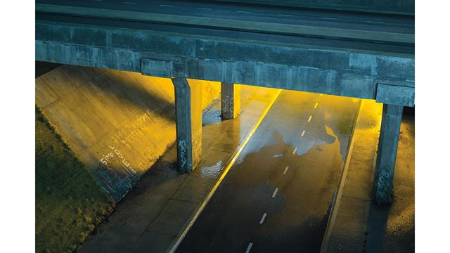 A road crossing beneath a motorway bridge, illuminated at night, with graffiti on the walls.