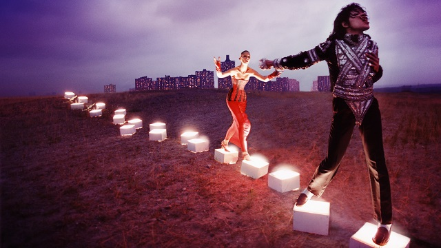 Michael Jackson steps on illuminated boxes in a field with a woman in a red dress and a city behind him.